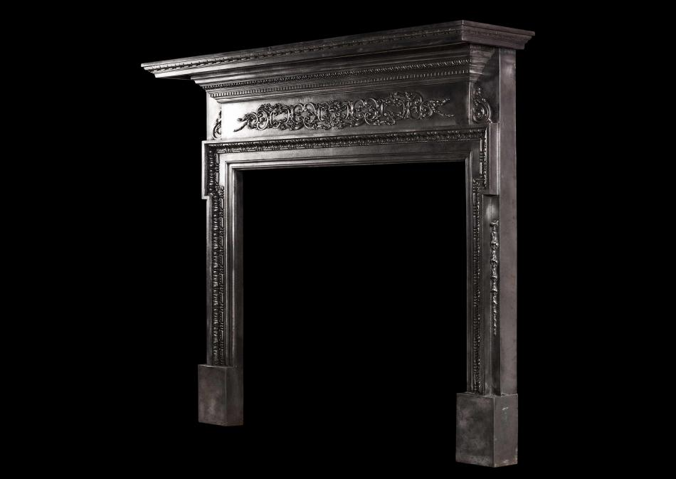 A cast iron fireplace with filigree frieze