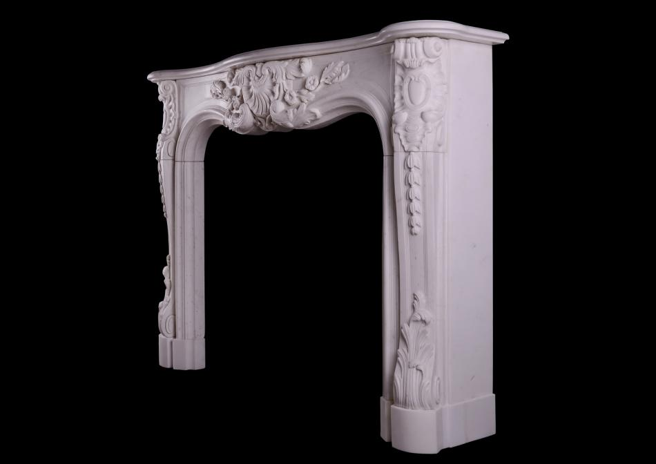 A heavily carved French Louis XV style fireplace