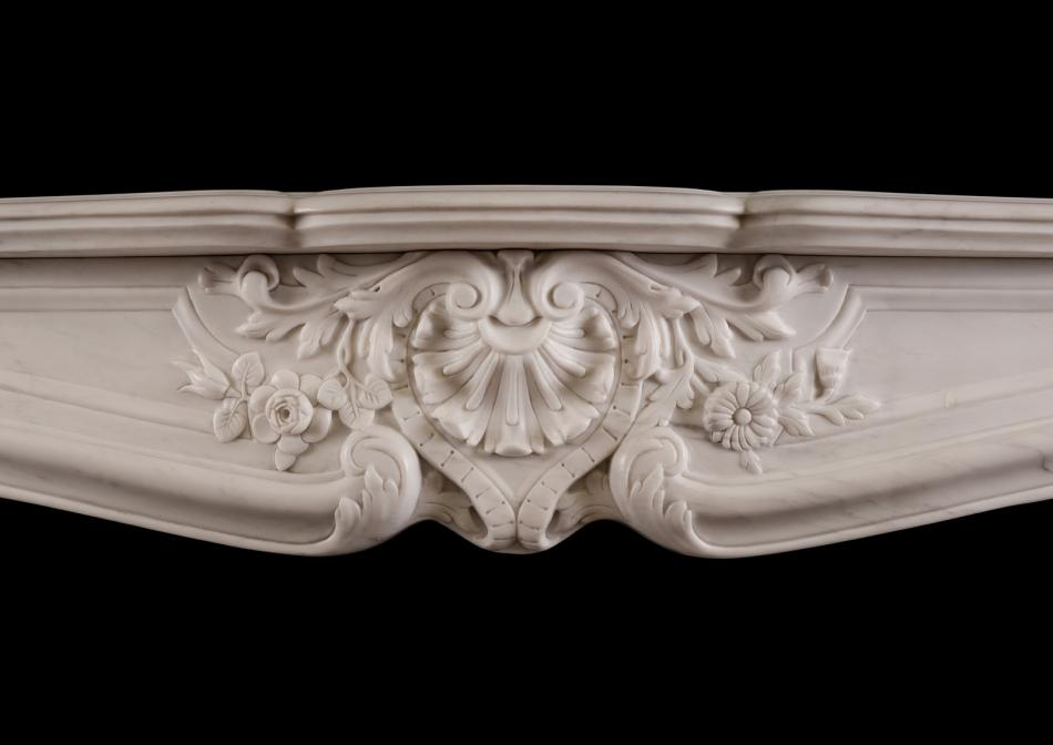 An ornately carved Louis XV marble fireplace