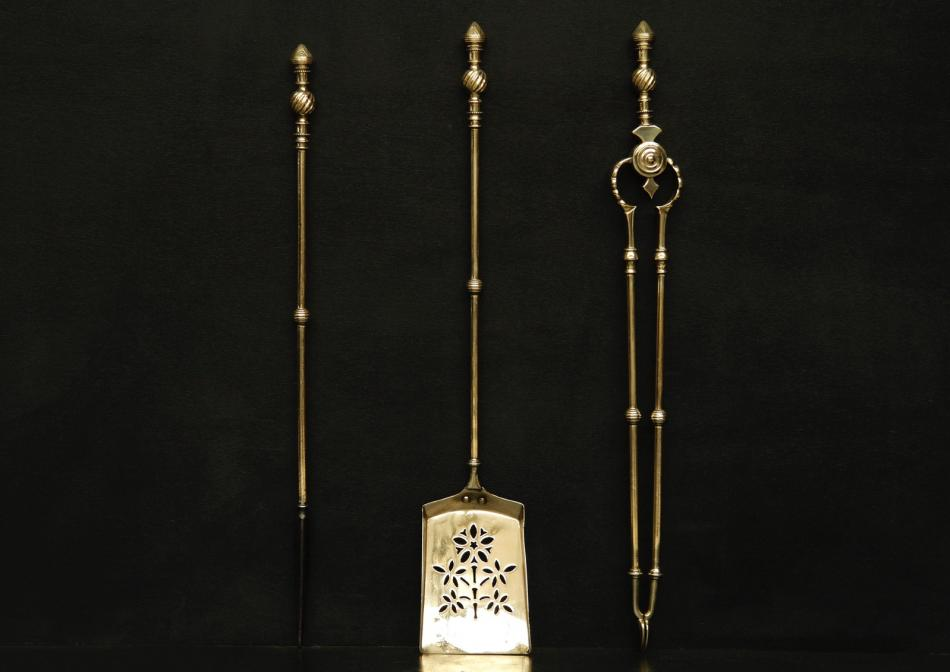 A set of brass firetools with decorative finials