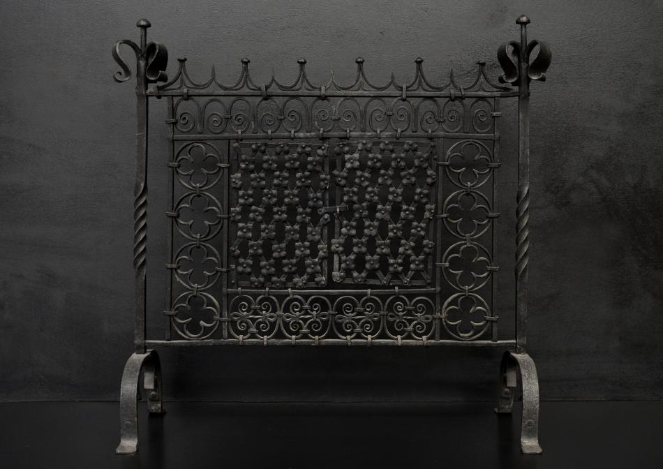 A large wrought iron firescreen in the Gothic taste