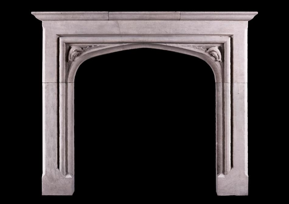 A small scale Gothic fireplace with carved dolphins