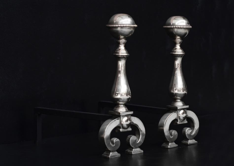 A pair of polished steel firedogs with beading to top