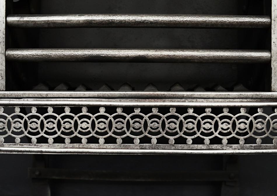 A polished steel firegrate with guilloche fret