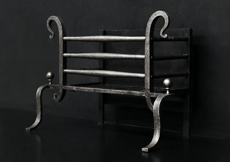 An English cast iron firebasket with shepherd's crook finials