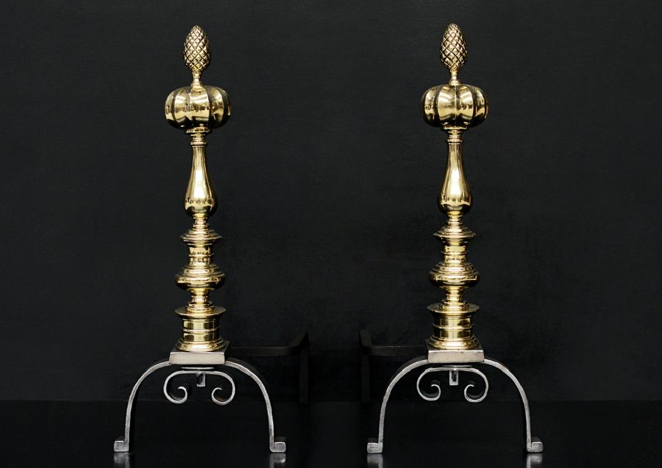 A pair of brass and steel firedogs