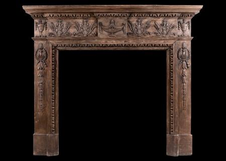 AN ENGLISH CARVED WOOD FIREPLACE IN THE LATE GEORGIAN STYLE