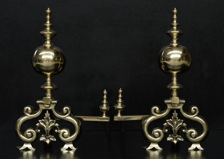 A pair of large brass firedogs
