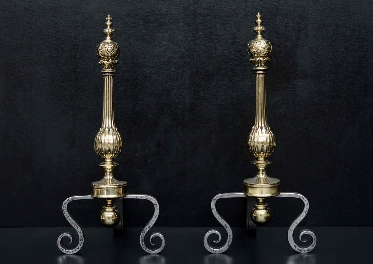 A pair of polished brass and wrought iron firedogs