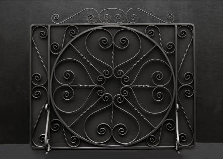 A LARGE ENGLISH WROUGHT IRON FIRESCREEN