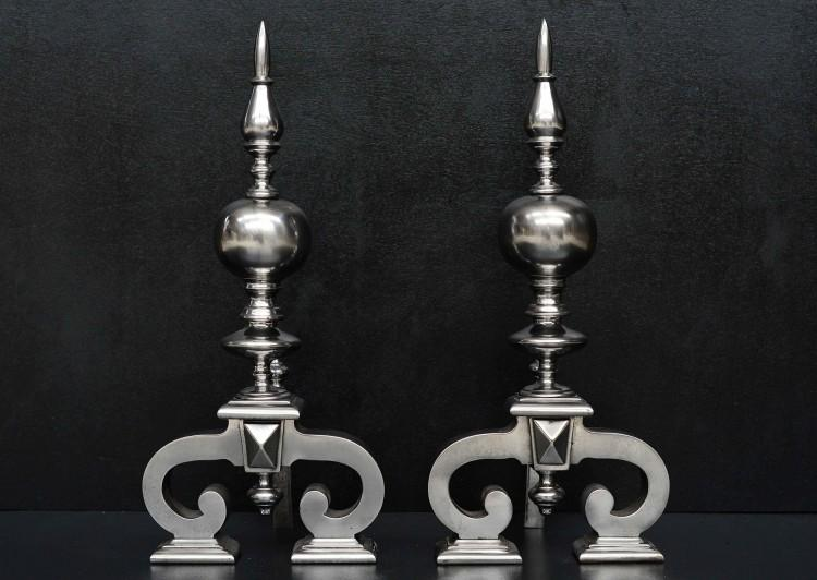 A large pair of antique polished steel firedogs