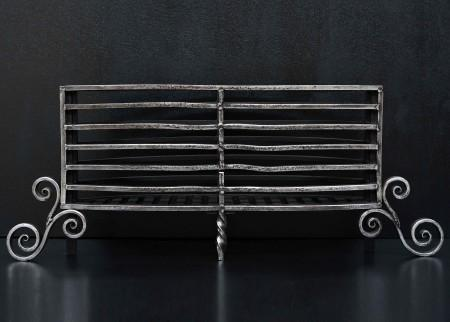 A SHAPED, POLISHED WROUGHT IRON FIREGRATE WITH SCROLLED FEET