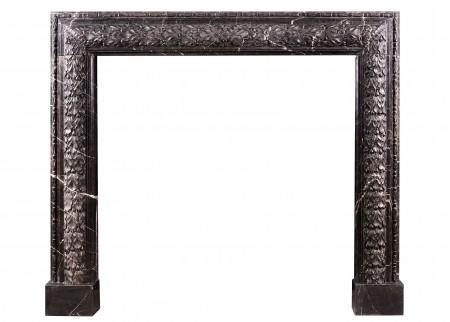 AN ELEGANT CARVED BOLECTION FIREPLACE IN NERO MARQUINA MARBLE