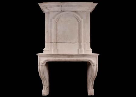 A EARLY 18TH CENTURY FRENCH LOUIS XIV LIMESTONE FIREPLACE WITH PANELLED TRUMEAU