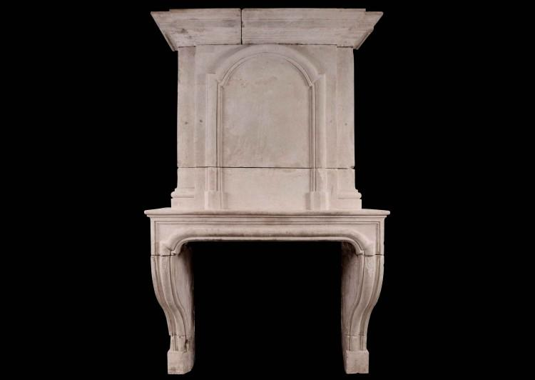 An early 18th century French Louis XIV limestone fireplace with panelled trumeau