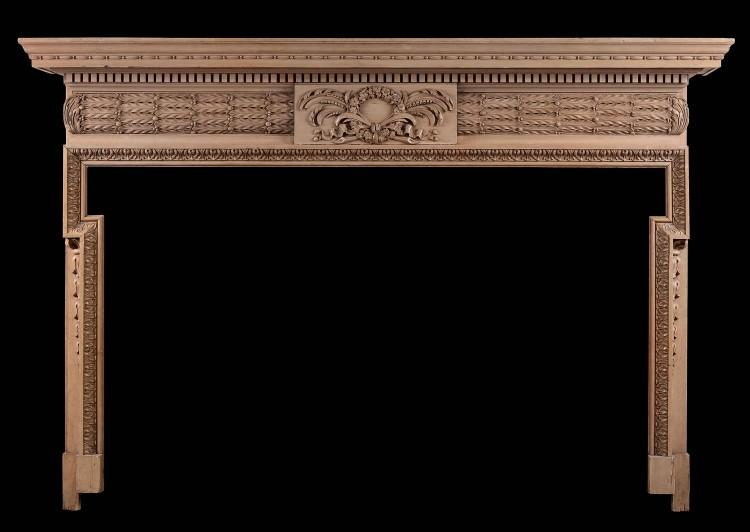 A well carved English pine fireplace with barrell frieze and oak leaves