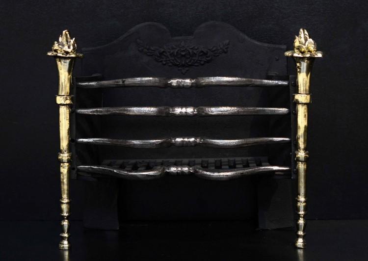 An English firegrate with brass torch finials