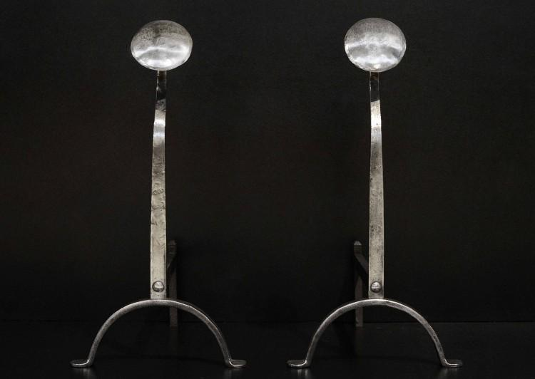 An elegant pair of polished steel firedogs