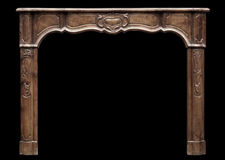 An elegant walnut French Louis XV style fireplace