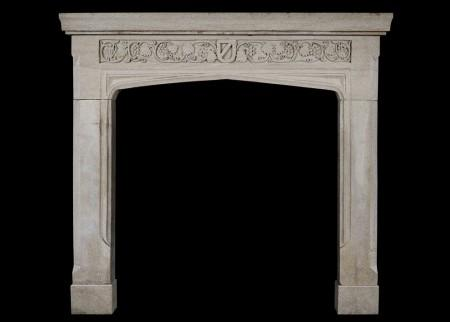 AN ENGLISH GOTHIC STONE FIREPLACE WITH CARVED FRIEZE