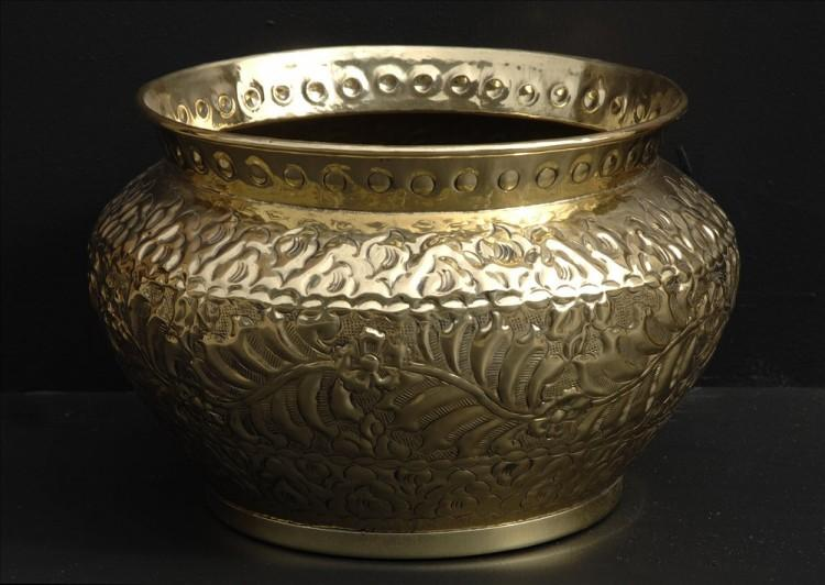 A brass coal bucket with repouse design