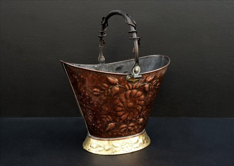A copper coal bucket with brass base