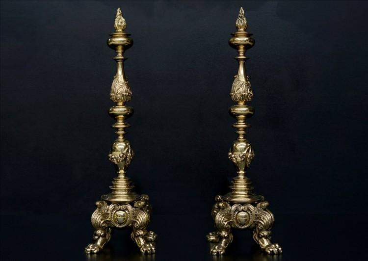A large pair of ornate brass firedogs