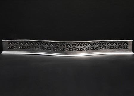 A 19TH CENTURY POLISHED STEEL FENDER WITH AETHENIAN MOTIF