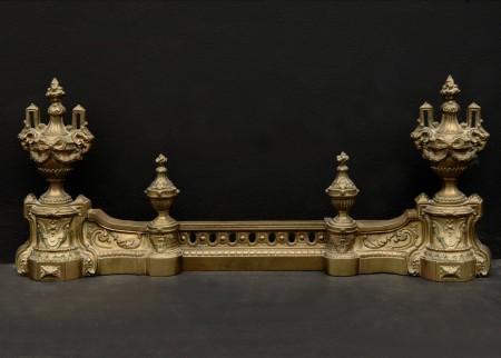 A DECORATIVE BRASS FRENCH FENDER WITH URNS