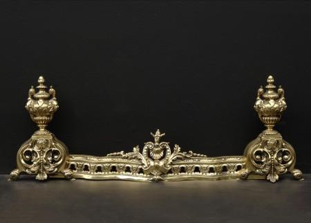 A DECORATIVE BRASS FRENCH FENDER WITH URN FINIALS