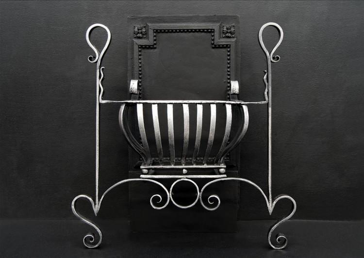 An Art Nouveau firegrate with scrolled legs and uprights