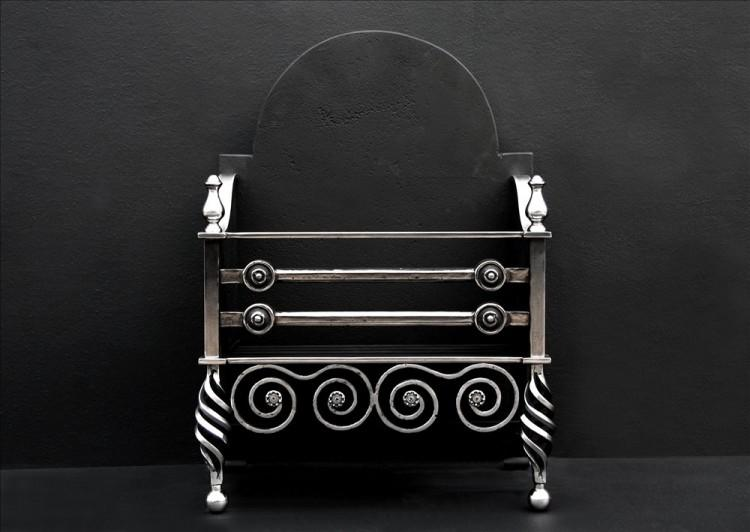 An English Arts and Crafts polished iron firegrate