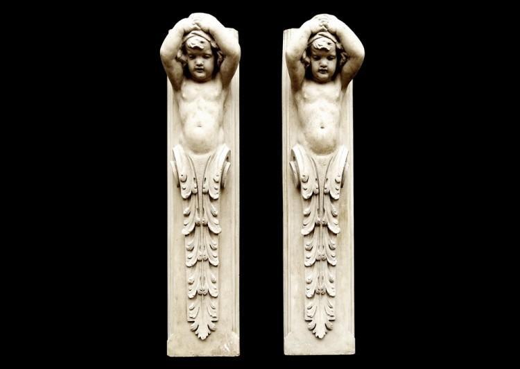 A pair of 19th century English glazed terracotta cherub figures