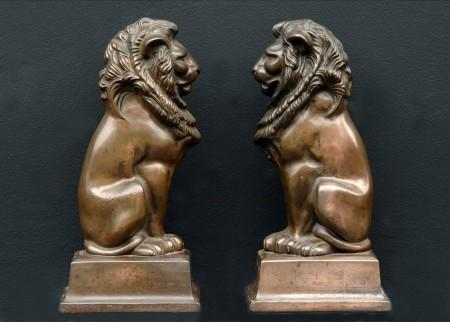 A PAIR OF FIREDOGS WITH LION MOTIF