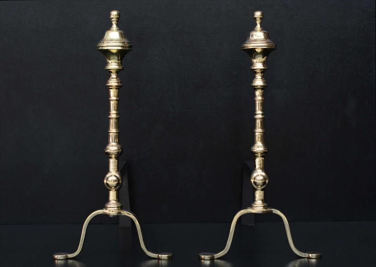 A pair of elegant polished brass firedogs