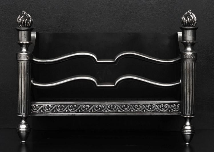 A polished steel firebasket with tapering legs and flame finials