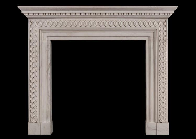 A white marble fireplace with guilloche carving