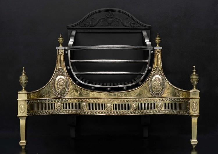 A large and impressive Adam style firegrate with brass adornments