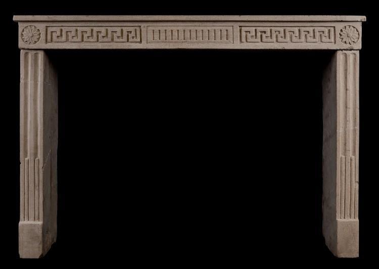 A rustic limestone Louis XVI fireplace