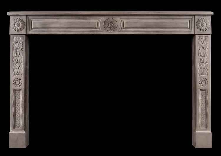 A rustic Louis XVI style limestone fireplace