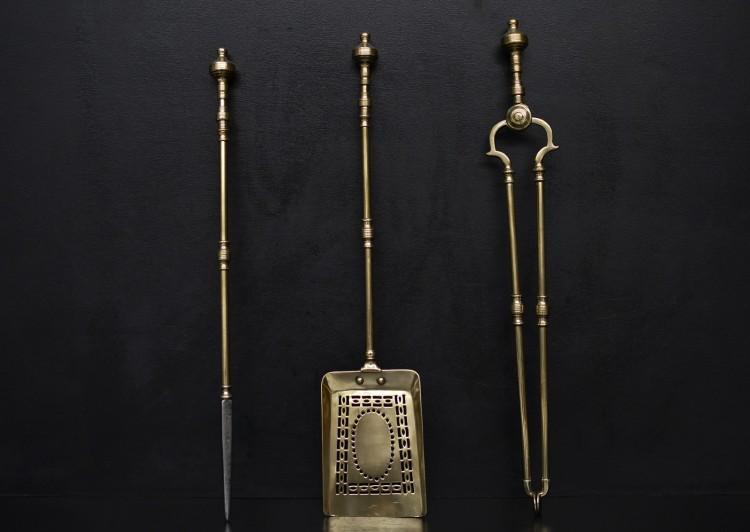 A set of polished brass firetools