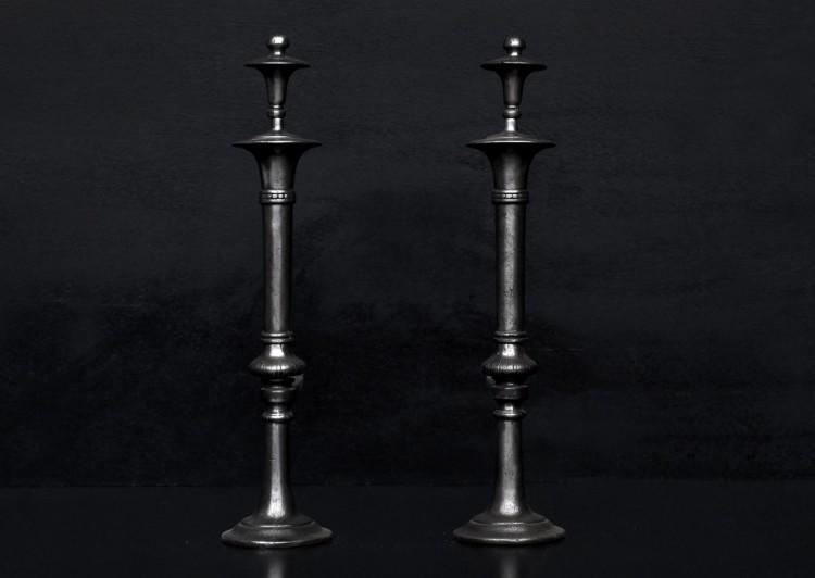 A pair of polished cast iron firedogs