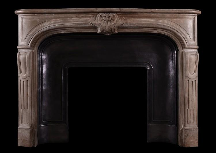 A transitional French Louis XIV / XV limestone fireplace