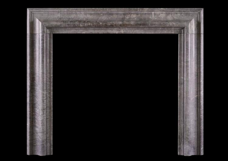 An antique bolection fireplace in grey marble
