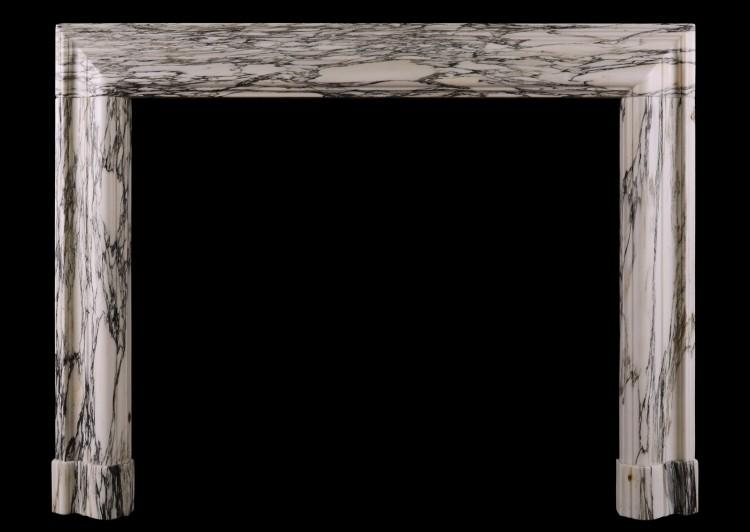 A striking veined marble bolection fireplace