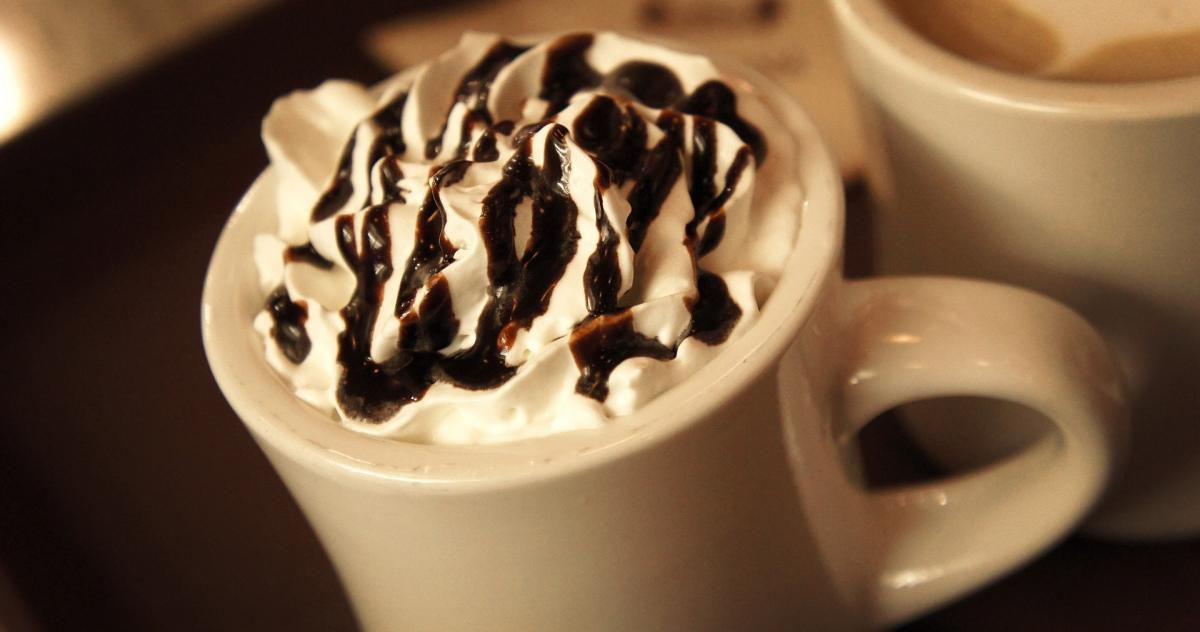 A mug of hot chocolate with cream and chocolate sauce