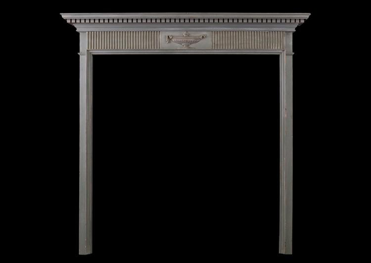 A small Regency wood fireplace with carved urn