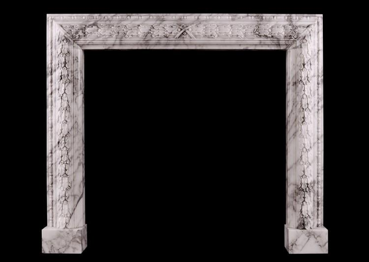 A carved bolection fireplace in Arabescato marble