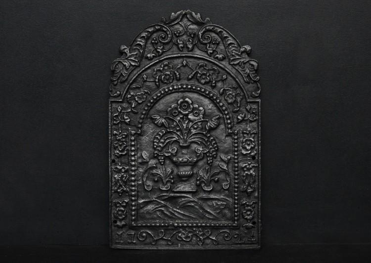A decorative cast iron fireback